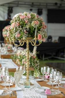Mesa com arranjo de flores e louças em evento social no event garden