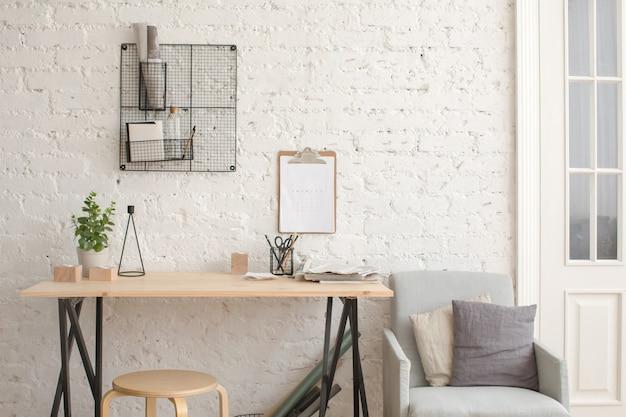 Mesa com artigos de papelaria no interior branco loft