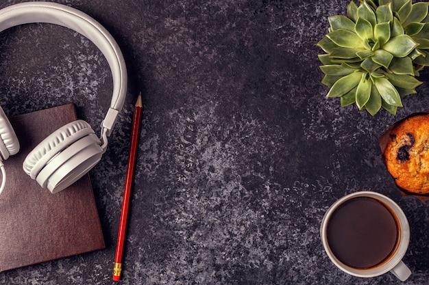 Mesa com bloco de notas, fones de ouvido e café.