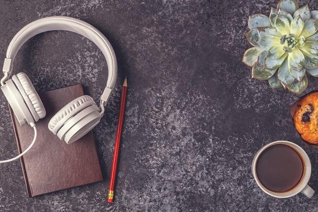 Mesa com bloco de notas, fones de ouvido e café