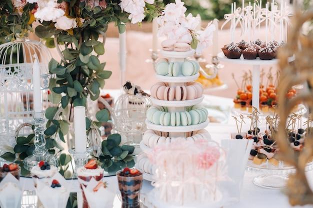 Mesa com bolos e doces na festa.