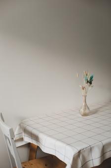 Mesa com buquê de flores e cadeiras