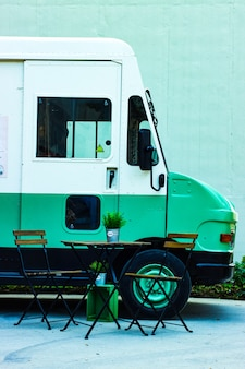 Mesa com cadeiras ao lado de um caminhão de alimentos