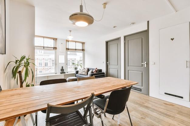 Mesa com cadeiras e sofá confortável localizado em sala espaçosa com decoração elegante em apartamento moderno
