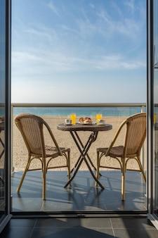 Mesa com café da manhã e duas cadeiras na varanda de um hotel na praia