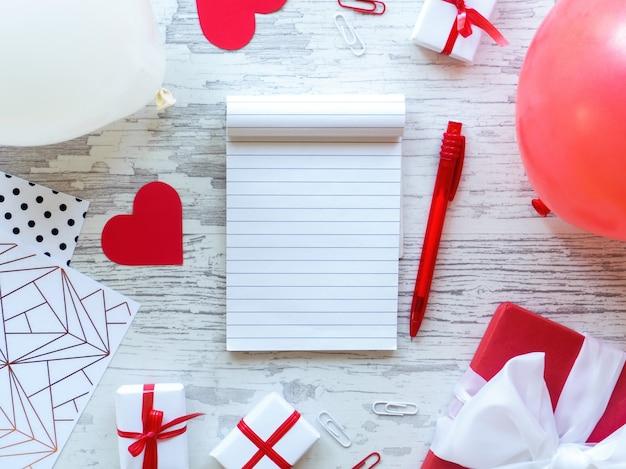 Mesa com caixas de presente, caderno, papelaria, balões, corações vermelhos