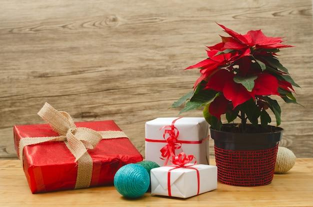 Mesa com cajas de regalos de navidad y maceta con flor de pascuas