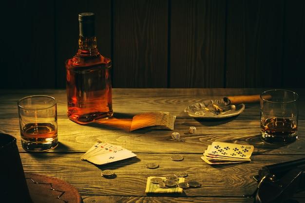 Mesa com cartas de jogar, uísque, charuto e armas