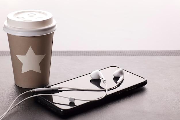 Mesa com copo de café quente telefone com fones de ouvido