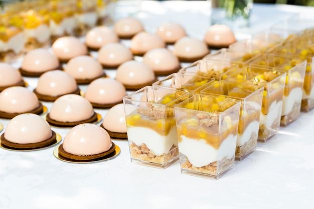 Mesa com doces decorada com flores e bolos de macaroon e sobremesas light em copos