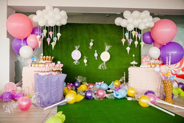 Mesa com doces e sobremesas, nuvem de balões e sorvetes