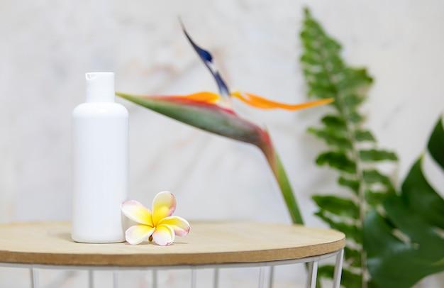Mesa com garrafa branca clara e folhas de palmeira verde sobre parede de mármore