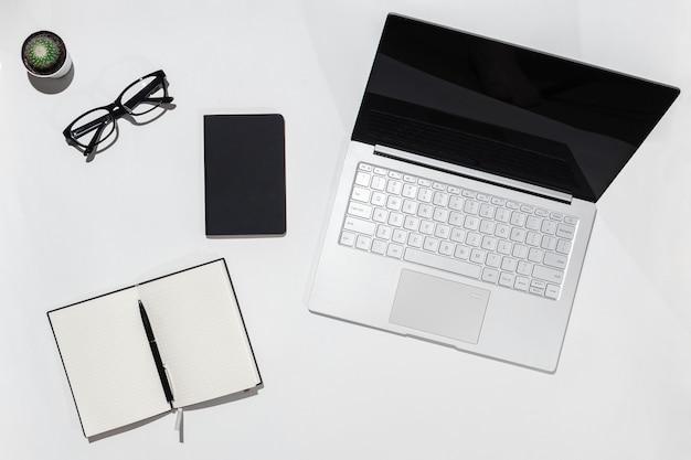 Mesa com laptop, caderno com caneta e óculos