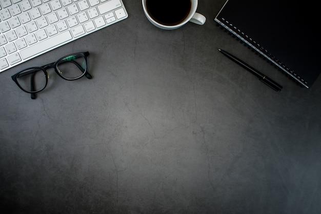 Mesa com laptop, café, teclado e acessórios