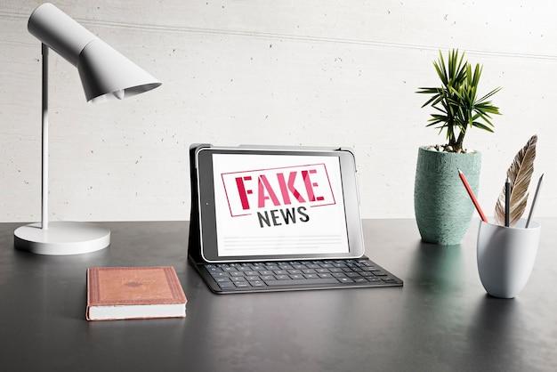 Mesa com laptop e notícias falsas