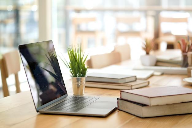 Mesa com laptop, livros e escritório de negócios.