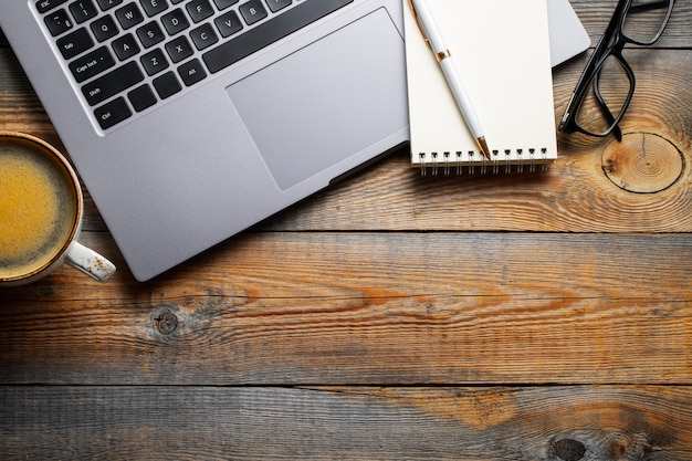 Mesa com laptop, óculos e uma xícara de café.