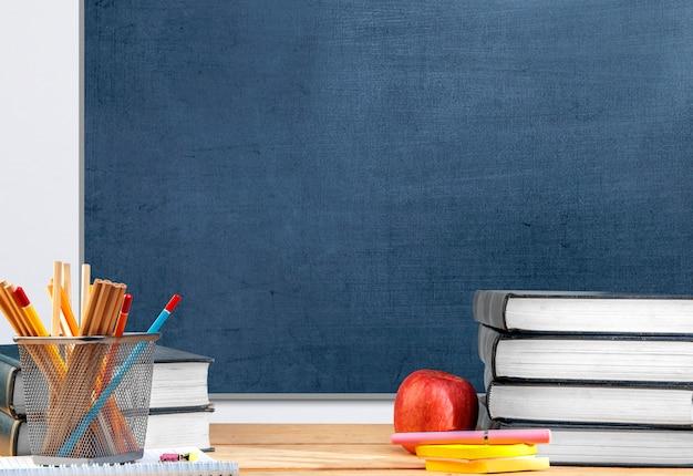 Mesa com livro e artigos de papelaria com fundo de quadro-negro. conceito de volta às aulas