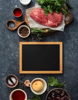 Mesa com lousa em branco e carne de bovino, legumes e especiarias