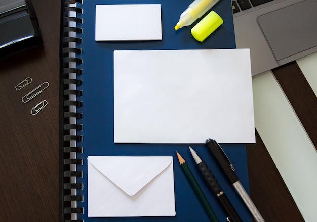 Mesa com material de trabalho de escritório em ordem e envelopes em branco e cartões para design de texto