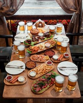 Mesa com muitos petiscos e cerveja