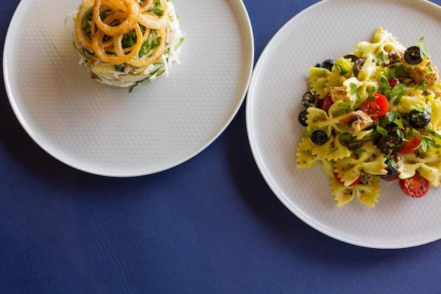 Mesa com muitos vista superior da salada. saladas diferentes na mesa de concreto, vista superior. salada de legumes, salada com salmão fumado, ceviche e stracciatella.