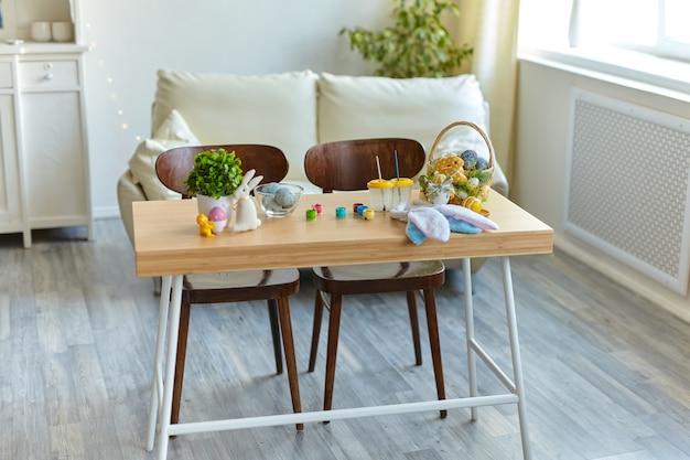 Mesa com ovos de páscoa coloridos e tinturas no interior da sala perto da janela