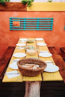 Mesa com pães e arroz em um hostel cheio de pratos para servir o jantar