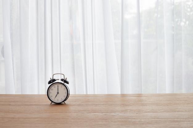 Mesa com relógio retrô de alarme no fundo da janela de cortina branca
