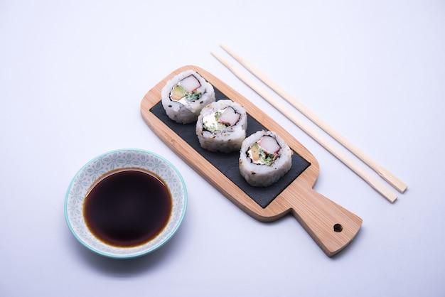 Mesa com sushi e pauzinhos com tigela de molho de soja