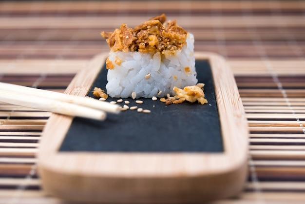 Mesa com sushi e pauzinhos no bambu