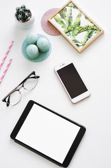 Mesa com tablet perto de smartphone, moldura, velas e óculos