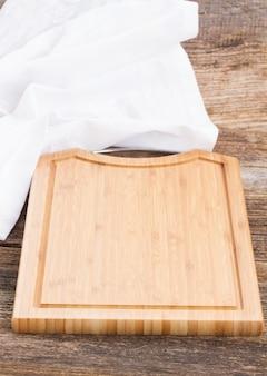 Mesa com tábua de madeira vazia e guardanapo de pano branco