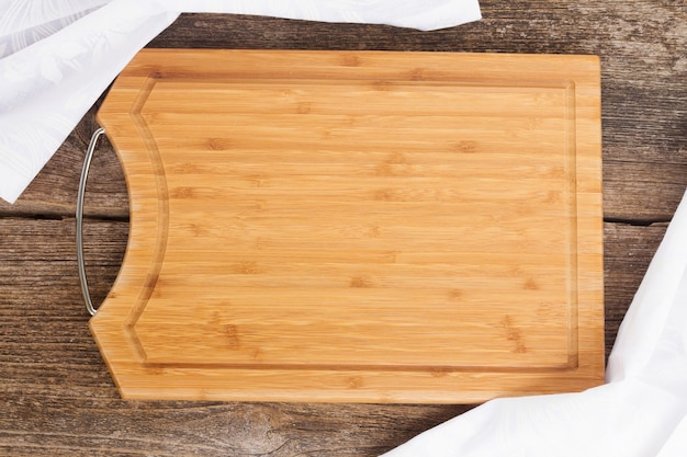 Mesa com tábua de madeira vazia e guardanapo de pano