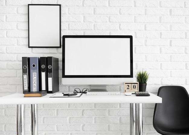Mesa com tela de computador e cadeira