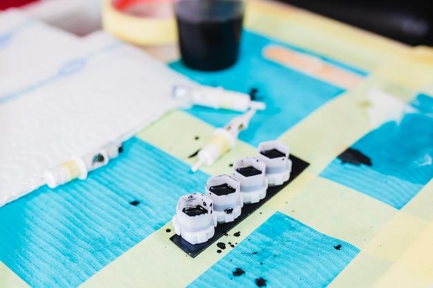 Mesa com tintas pretas e toalhetes