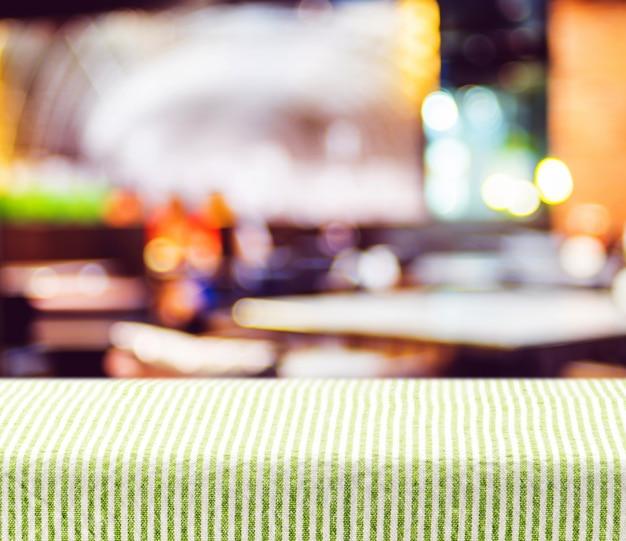 Mesa com toalha de mesa verde com fundo do restaurante borrão