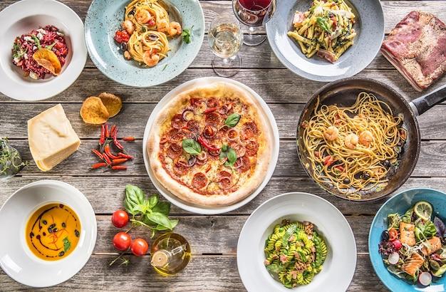 Mesa completa de cima da vista de refeições italianas em pratos e panelas. sopa de risoto de massa de pizza e salada de vegetais de peixe.
