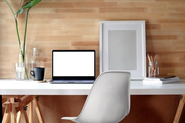 Mesa contemporânea do espaço de trabalho com portátil e cartaz na mesa.