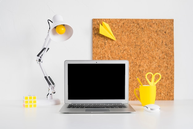 Mesa criativa com placa de cortiça e laptop