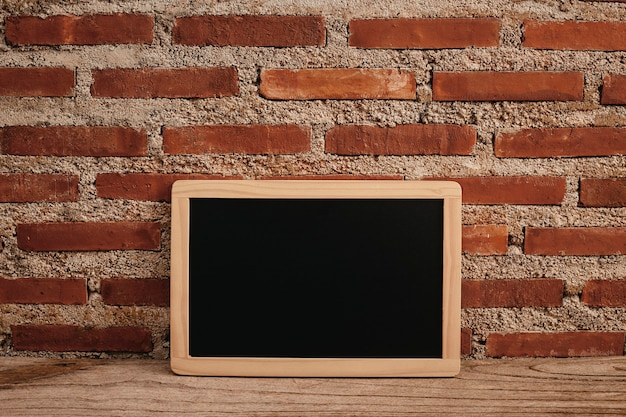 Mesa criativa de escritório com quadro de correspondência na mesa de madeira e parede de tijolos brancos
