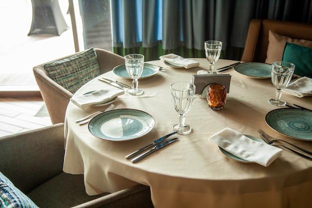 Mesa curada no restaurante, pratos de talheres com copos