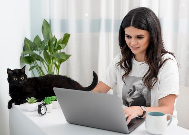 Mesa da mulher em casa que trabalha e com gato