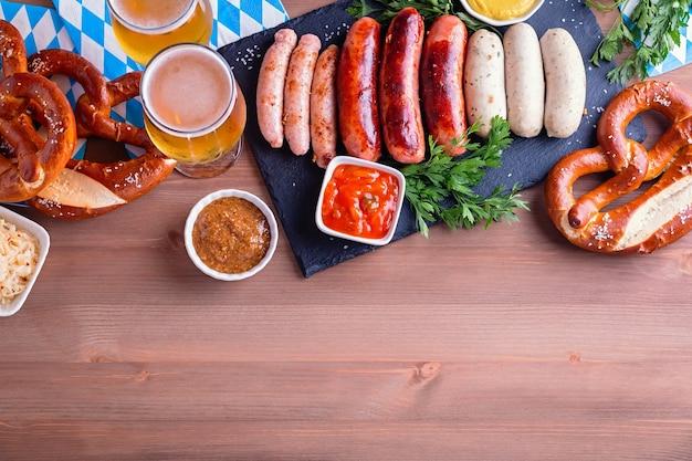 Mesa da oktoberfest com comida tradicional. salsichas assadas, pretzels, cerveja, repolho azedo, mostarda em fundo de madeira, vista superior, espaço de cópia, banner da web