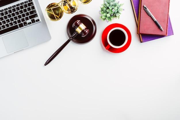 Mesa de advogado branco com laptop, livro, caneta, xícara de café, juiz de martelo e símbolos da lei.