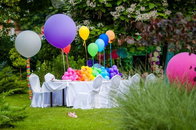 Mesa de aniversário com balões de arco-íris. férias de verão no parque.