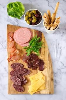 Mesa de aperitivo para vinho ou cerveja com salsichas, carne seca e queijo
