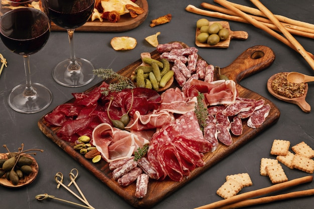 Mesa de aperitivos com diferentes antepastos, queijo, charcutaria, lanches e vinho. salsicha, presunto, tapas, azeitonas, queijo e bolachas para buffet.