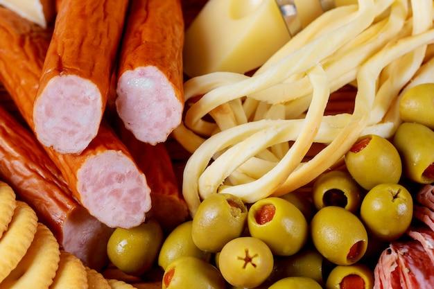 Mesa de aperitivos com queijo de azeitonas e salsichas e placa de variedade de carne vista superior