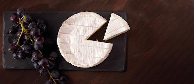 Mesa de aperitivos com queijo francês camembert e uvas para buffet de aperitivos